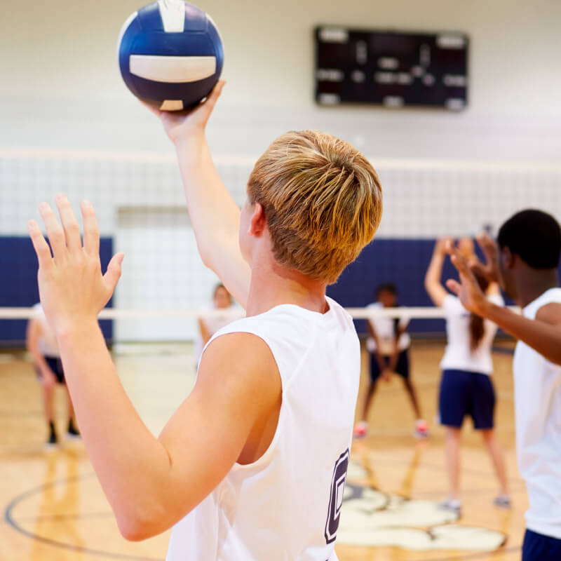 students playing volleyball in gymnasium
